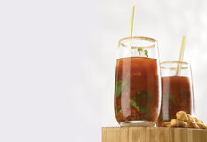Coriander bloody Cesar. Two coriander bloody Cesar Asian style on wood board with cheese twirls Royalty Free Stock Images