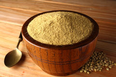 Coriander Powder. In a wooden bowl on a wooden background Stock Images