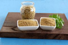 Coriander Powder in Ceramic Bowls and Coriander Seeds and Leaves. Coriander powder in two ceramic bowls and coriander leaves on a wooden table and seeds in a royalty free stock images