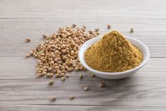 Coriander seed and powder. On wooden texture background Stock Photo