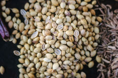 Coriander seeds on black metal plate surrounded by spices. Stock Image