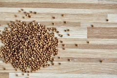 Coriander seeds heap over the light wooden background, close-up, top view, macro, selective focus. Some copy space for your inscription. Natural antioxidant Stock Image