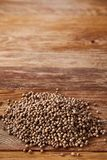 Coriander seeds heap over the rustic wooden background, close-up, top view, macro, shallow depth of field. Coriander seeds heap over the rustic wooden Stock Photography