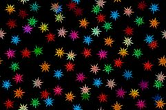 Coriandoli colorati delle stelle su un fondo nero Fotografia Stock