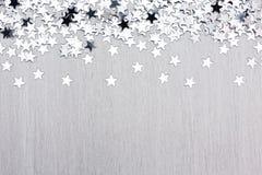 Coriandoli della stella sul fondo d'argento del metallo Fotografia Stock Libera da Diritti