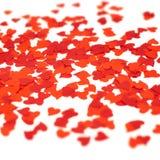 Coriandoli rossi a forma di sparsi del cuore Immagini Stock