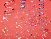 Coriandoli rossi, gialli e verdi del cerchio e del cuore su un fondo ROSSO Foto di alta risoluzione Fotografie Stock