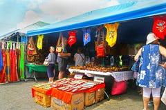 Corinto, Nicarágua 10 de outubro de 2018 Turistas que consultam em lojas com bens coloridos, roupa, camisas de T, lembranças fotografia de stock royalty free