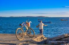 Corinto Nicaragua - Maj 16, 2018: Oidentifierad man med hans cykel som tycker om sikten av fiskebåtar i havet, under Royaltyfri Bild