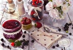 Corinto preto, doce da morango e de cereja com rosas, frascos do vintage e colher Imagem de Stock Royalty Free