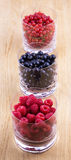 Corintos pretos, vermelhos e framboesas nos vidros Fotografia de Stock Royalty Free