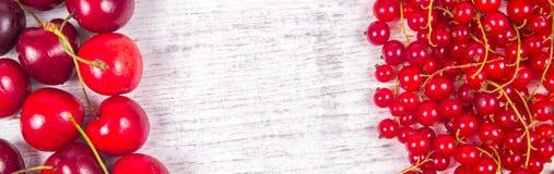 Corintos vermelhos e cerejas maduros frescos no fundo de madeira rústico Foto de Stock