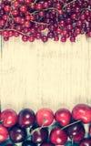 Corintos vermelhos e cerejas maduros frescos no fundo de madeira rústico Fotos de Stock Royalty Free