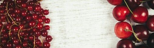 Corintos vermelhos e cerejas maduros frescos no fundo de madeira rústico Fotografia de Stock Royalty Free