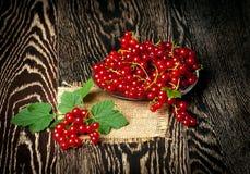Corintos vermelhos frescos com as folhas no fundo de madeira Fotografia de Stock