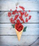 Corintos vermelhos frescos maduros no cone do waffle do gelado no fundo de madeira rústico Imagem de Stock