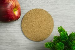 Cork Board with Apple and Potted Plant on Wood Background. Cork board on light wood background with apple and potted plant Royalty Free Stock Photos