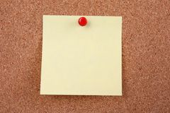 Cork board with blank note. Attached with thumb pin Royalty Free Stock Image