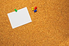 Cork board with a blank piece of paper ready to write messages. Empty space for text pinned on a cork board royalty free stock image