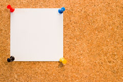 Cork board with clear white blank notice with the colorful pins. Cork board with clear white blank notice with the colorful four pins stock photography