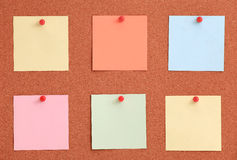 Cork board with colorful notes and red pin Stock Photos