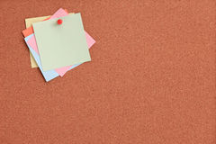 Cork board with colorful notes and red pin Royalty Free Stock Images