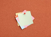 Cork board with colorful notes and red pin Royalty Free Stock Photos