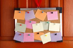 Cork board with colorful papers and push pins hanging by a door Royalty Free Stock Photos
