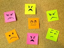 Cork board with colorful post its representing various emoticons with anger emotion communication accusing concept. Photo stock photos