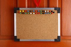 Cork board with colorful push pins hanging by a door Royalty Free Stock Image