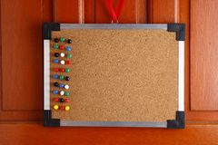 Cork board with colorful push pins hanging by a door Royalty Free Stock Images