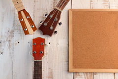 Cork board with copy space  and ukuleles. On the wooden deck Royalty Free Stock Images