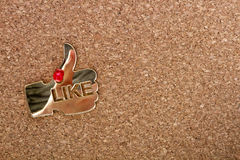 Cork-board with a like icon. Big golden thumb up shape made of plexiglas on a cork-board with a real human thumb up reflection on a shape surface royalty free stock photography