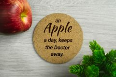Cork Board with Motivational Quote. An Apple a Day, Keeps the Doctor Away. An a apple a day keeps the doctor away. Cork board on light wood background with Royalty Free Stock Images