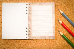 Cork board with a notepad and the colorful pencils Stock Photo