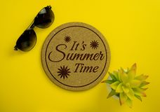 Cork Board with the Phrase `It`s Summer Time` with Sunglasses an. It`s Summer Time. Cork board, sunglasses and potted plant on yellow background Stock Image