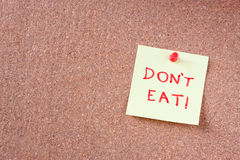 Cork board with pinned yellow note and the phrase dont eat written on it. room for text. Royalty Free Stock Images