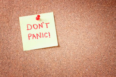 Cork board with pinned yellow note and the phrase dont panic written on it. room for text. Royalty Free Stock Photography