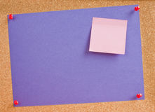 Cork board post it note purple announcement. Cork board with purple paper and pink post it note attached with red push in pins. Copy space for your announcement stock photo