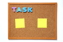 Cork board with task wording and paper note on white background Royalty Free Stock Photo