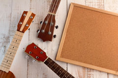 Cork board and ukuleles. In the white wooden terrace Stock Image