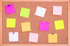 Cork board wood background with post it notes in different radiant colours. Cork board surface. Close up background of cork board. stock photos