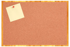 Cork board with yellow note and red pin Stock Photography