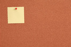 Cork board with yellow note and red pin Royalty Free Stock Photos