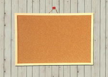 Cork bulletin board on wood wall Royalty Free Stock Image