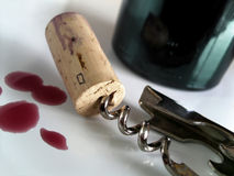 Cork Cap. Corkscrew with cork taken out from a wine bottle and some fallen wine drops Stock Photo