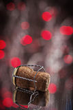 Cork of champagne on mirror surface with lights of red bokeh Royalty Free Stock Photo