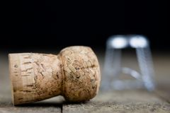 Cork from champagne on a wooden kitchen table. Good New Year's d. Rinks and great fun. Dark background Royalty Free Stock Images