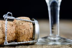 Cork from champagne on a wooden kitchen table. Good New Year's d. Rinks and great fun. Dark background Royalty Free Stock Photos