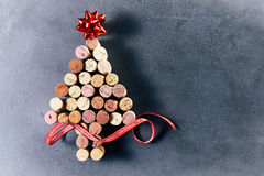 Cork Christmas tree with red star and ribbon. A Christmas tree made from used wine bottle corks with red star and decorative ribbon on dark background with copy Royalty Free Stock Images